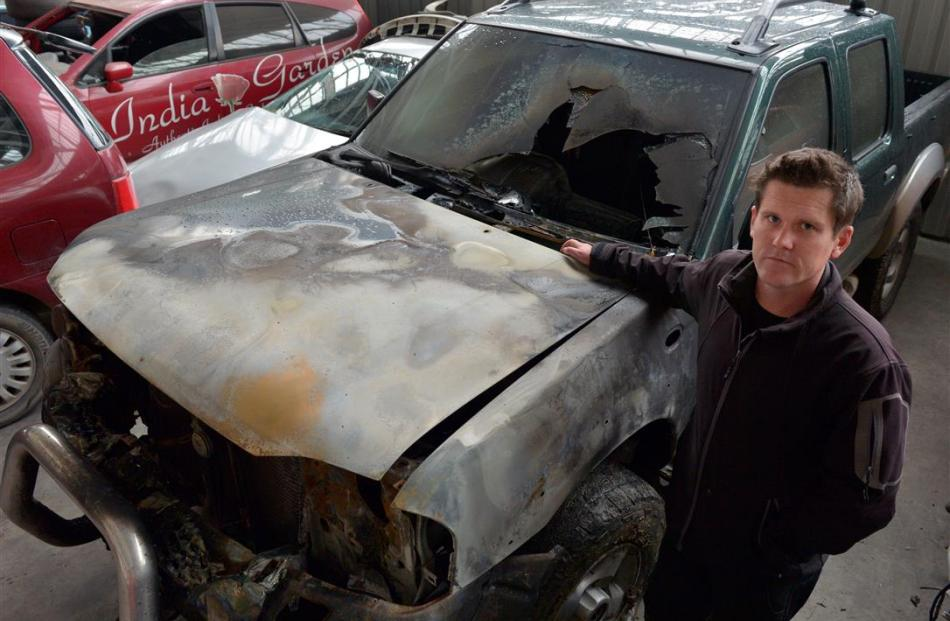 Richard Warrington stands next to his burnt-out Nissan Navara at Reilly's Towage and Salvage...