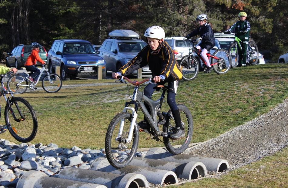 Finn Thomson (11), of Mount Aspiring College in Wanaka, steadies himself over obstacles at the...