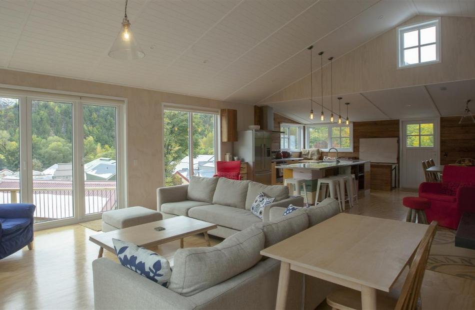 The open-plan living area has a raked ceiling, a woodburner with a waxed steel chimney and doors...