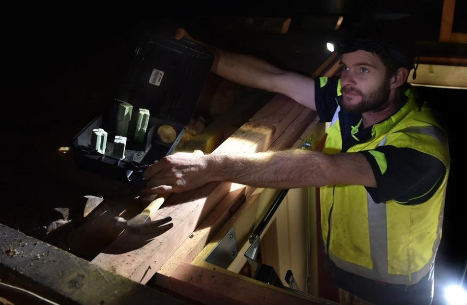 DM Holdings pest control operator Austin Finlayson places bait in an attic. Photo by Peter McIntosh.