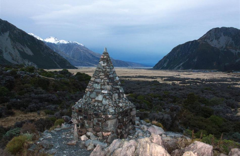 A stone cairn on a walking trail near Mount Cook Village bears plaques containing the names of...