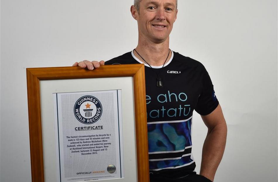 Dunedin cyclist Andrew Nicholson (45) holds his Guinness World Records certificate for being the...