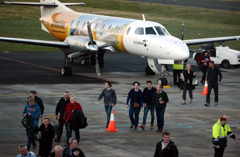 Passengers disembark from their late flight into Dunedin.