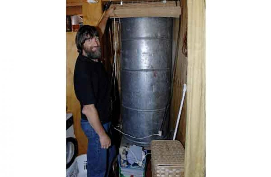 Mr Grimwood shows off the huge ex-industrial hot water cylinder in the bathroom.