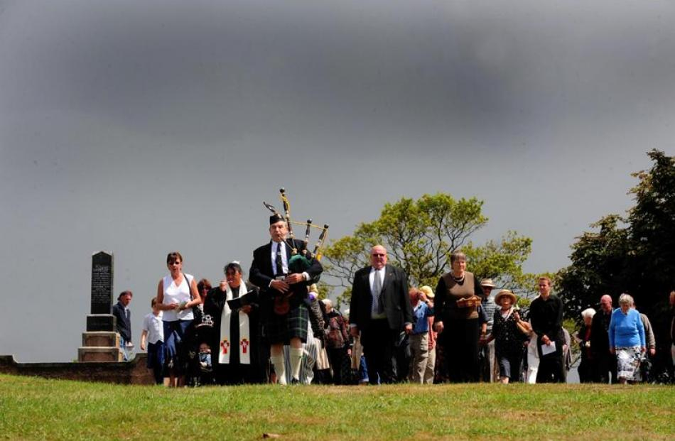 Bagpiper Max Wells leads family and guests to the grave.