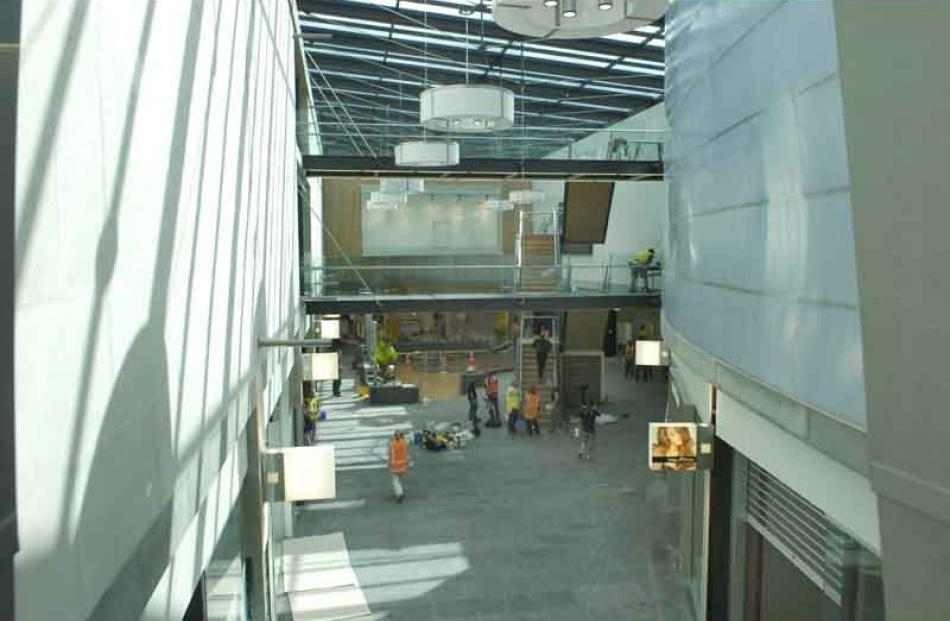 The heat-absorbing stone wall (left) is used to moderate the temperature inside the mall. The...