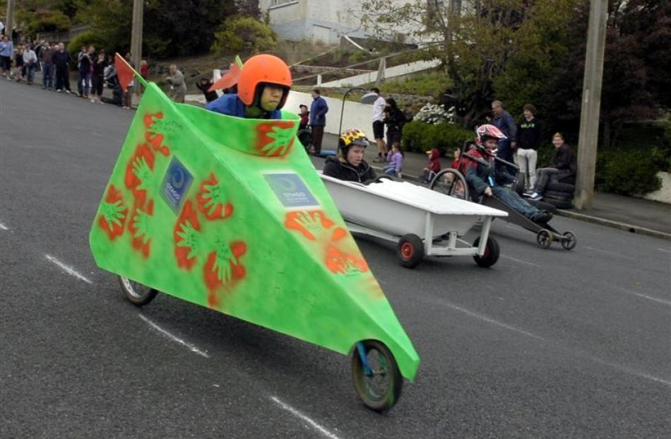 Nik Borland reaches the finish line in his wheeled bath tub during the Manor Pl Trolley Derby on...