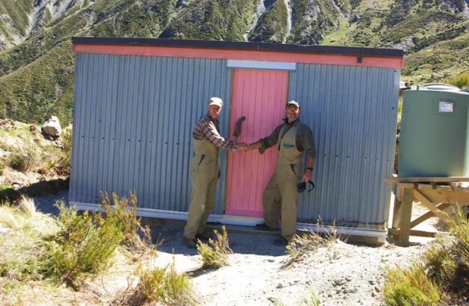 Mr Murfin (left) and Mr Hardie shake hands in front of the restored hut. Photo by DoC.