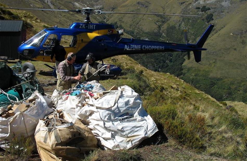 Packing up their kit for an airlift after restoring McIntyres hut in February are Doc Wakatipu...