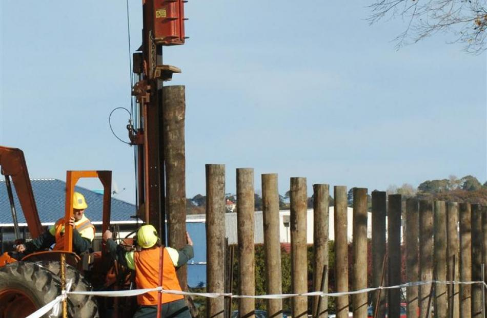 Hawkins Construction workers (top) use a pile-driver to install a security fence around the...