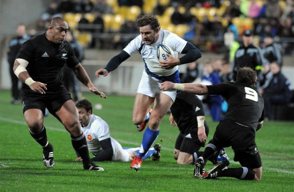 France's Cedric Heymans, centre, runs between New Zealand's Neemia Tialata, left and Jimmy Cowan....