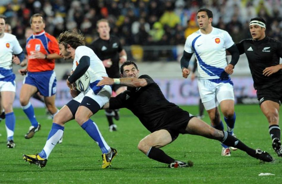 France's Maxime Medard , left, is tackled by New Zealand's Stephen Donald. Credit:NZPA / Ross...