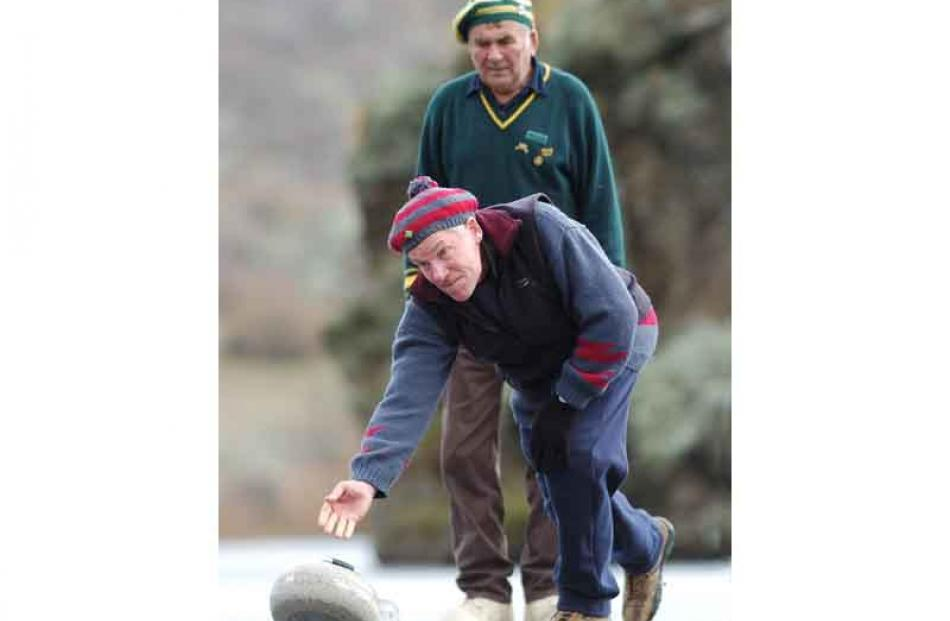 Pat Cooney (Chatto Creek) watched by Jack Davis (Lowburn) as he delivers his stone.