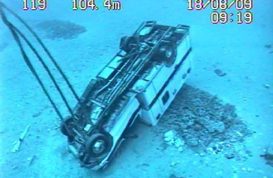 A vehicle lies where it fell from the vessel.