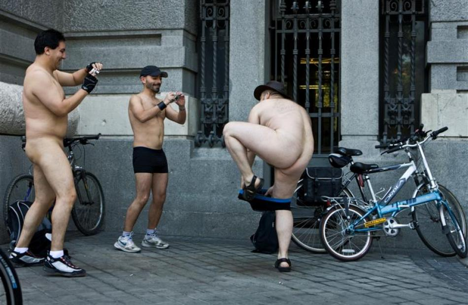 Cyclists takes snapshots of a fellow rider before riding naked through central Madrid. Photo by AP.