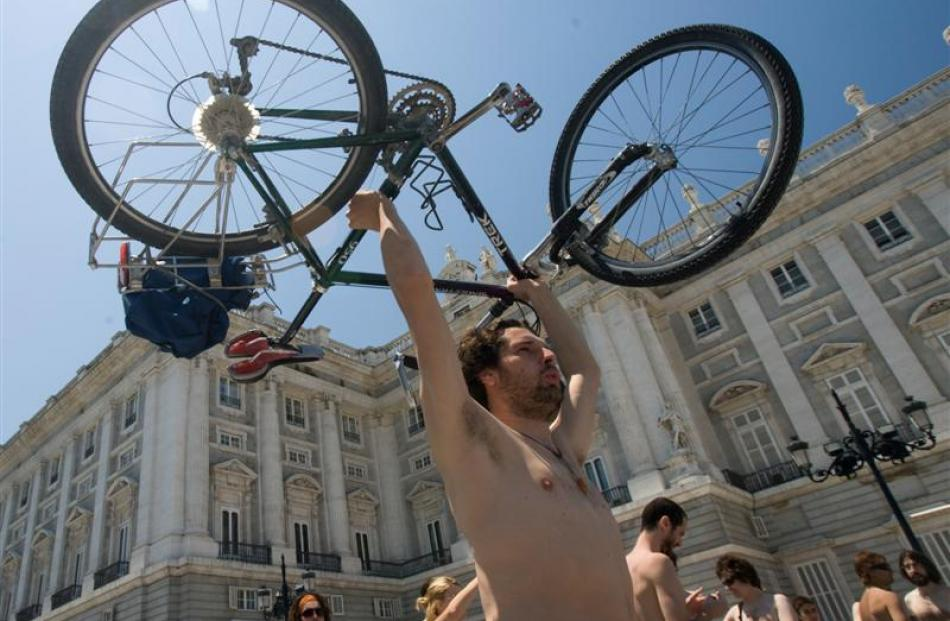 A cyclist shows his bicycle after riding naked through central Madrid. Photo by AP.