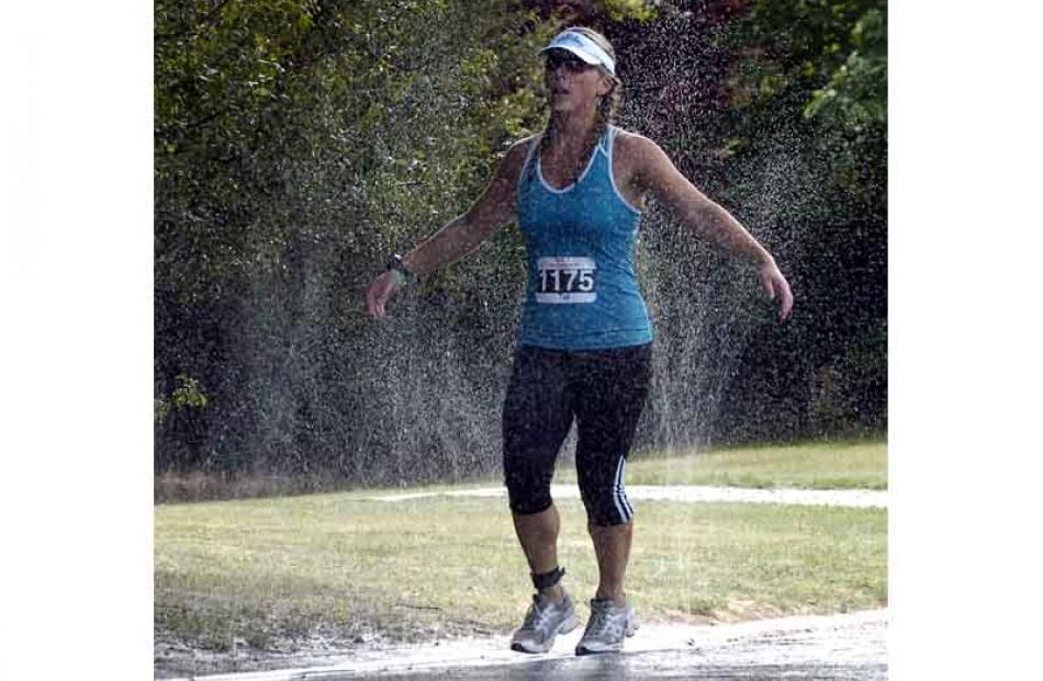 Tui Russell of Wanaka soaks up water from a roadside sprinkler. Photo by Jane Dawber.