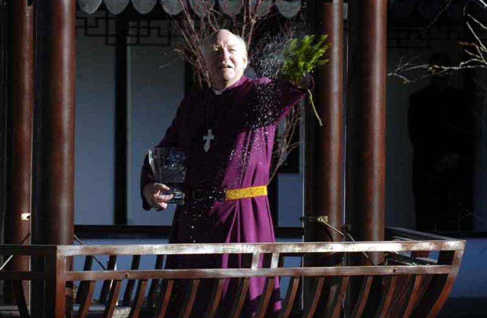 Anglican Bishop of Dunedin George Connor splashes water during a blessing ceremony.