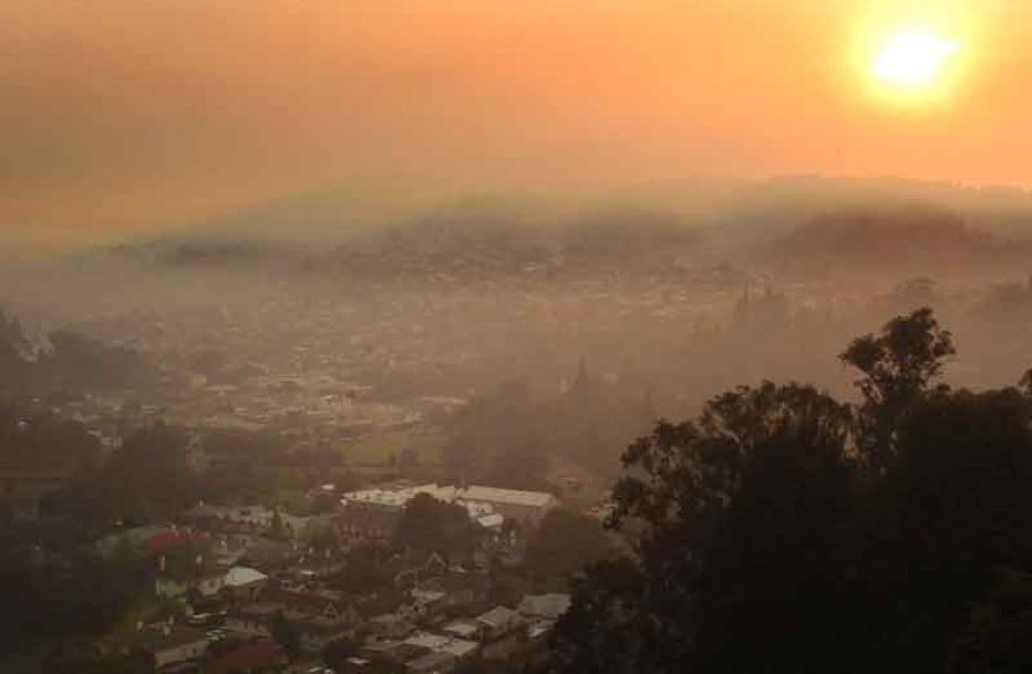 North East Valley is bathed in an eerie glow as morning sun shines through smoke yesterday. Photo...