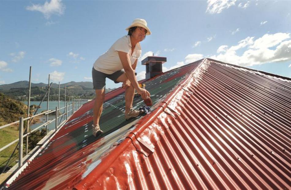 Former caretaker Kathy Morrison paints the roof.