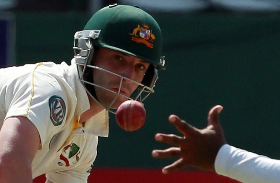Australian batsman Phillip Hughes watches as Sri Lanka's Lahiru Thirimanne tries to stop the ball...