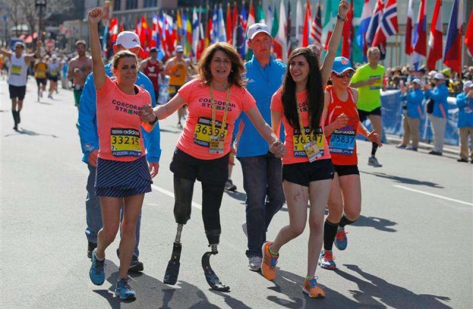 2013 Boston Marathon survivors Celeste Corcoran (centre) and her daughter Sydney (right) finish...
