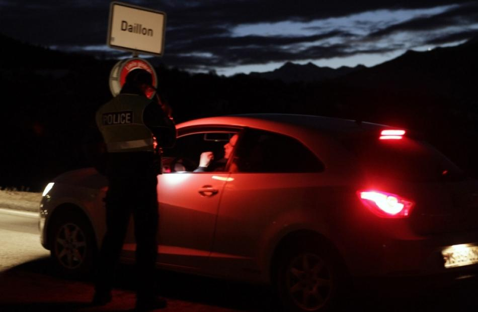 A policeman controls entering traffic at the entrance of the Swiss village of Daillon. Photo by...