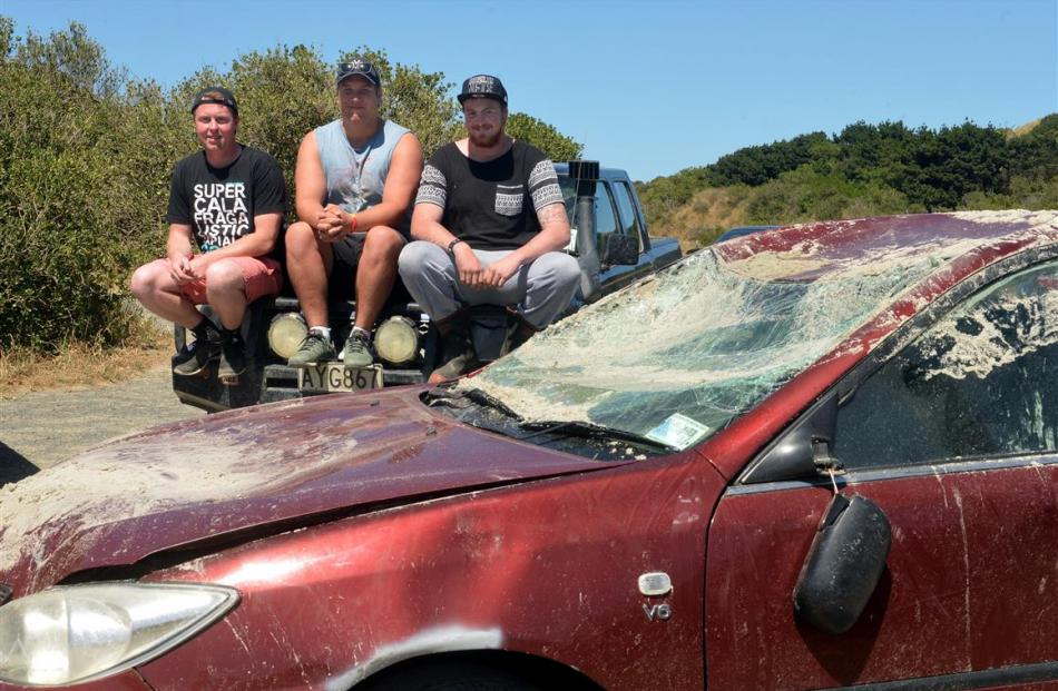 Inspecting the Toyota Camry they helped salvage from a Dunedin beach are (from left) Rhys...