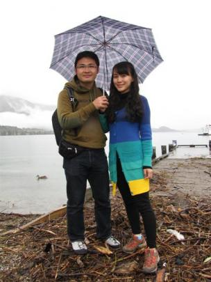 Lei Huang and Xlaolu Du, of China, did not mind the waterfront debris left by a swollen Lake...