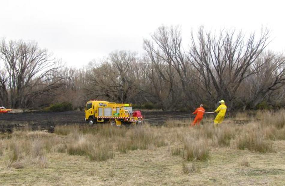 Volunteer firemen mop up after yesterday's estimated 2000sq m scrub fire in Springvale, near...
