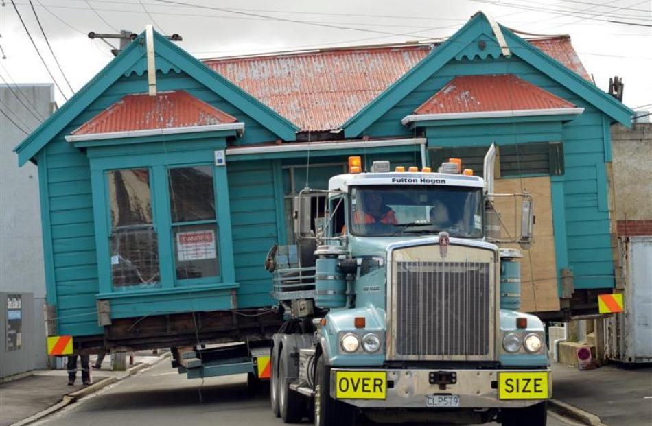 The cottage is moved along Braemar St, South Dunedin. Photo by Stephen Jaquiery.