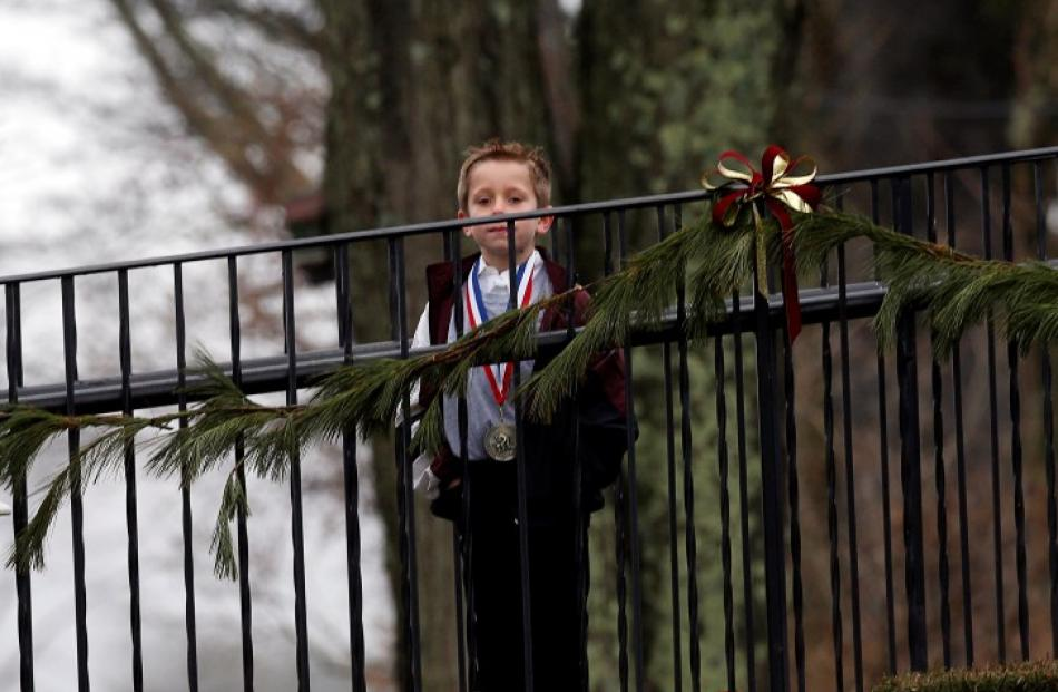 A boy waits to enter the funeral home where the family of six-year-old Jack Pinto, a victim of...