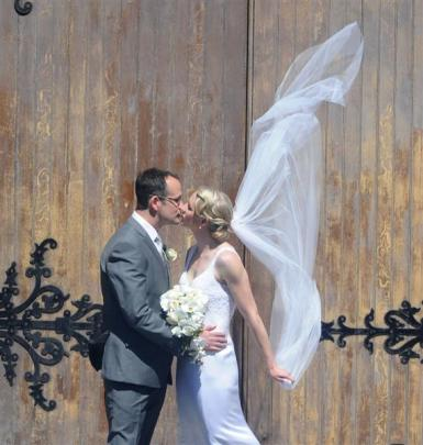 A breeze catches the veil of Alison Shanks' wedding dress as she kisses her husband Craig Palmer...