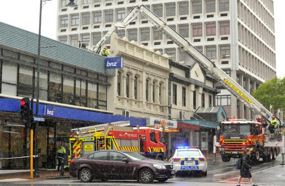 A cable running from  a George St  building across the street is taken down after a crack was...