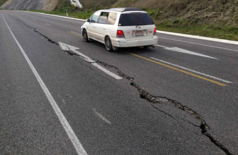 A car drives past a crack in a road after an earthquake on the outskirts of the town of Seddon in...