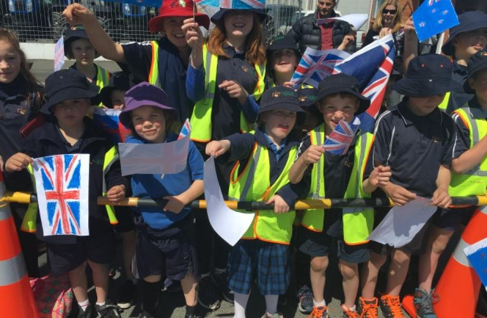 A crowd of around 500 people, many of them schoolchildren, wait to see the Royal couple in...
