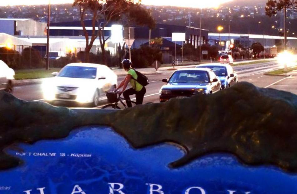 A cyclist waits to cross Portobello Rd as darkness descends on Dunedin. Photos by Dan Hutchinson