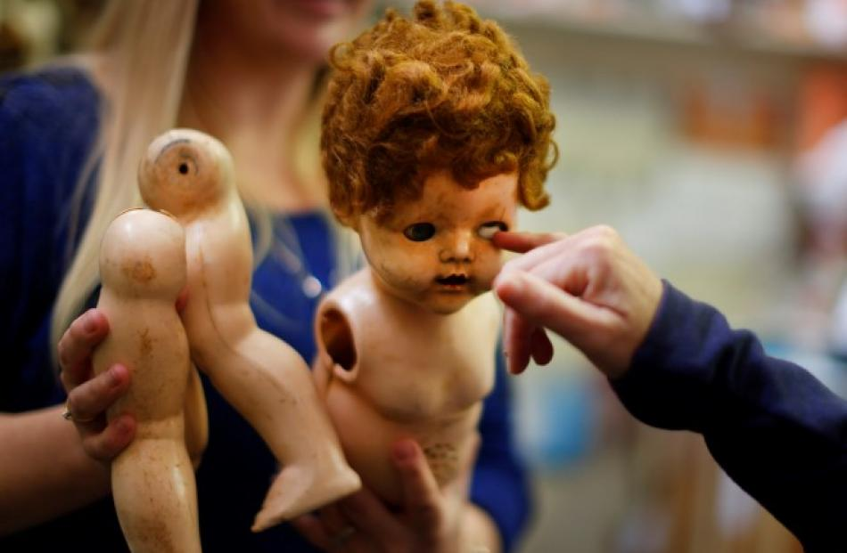 A damaged doll is brought in for repair by a customer at Sydney's Doll Hospital. Photos: REUTERS...