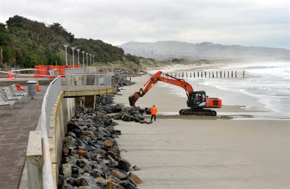 A digger (top) works to clear rocks from the bottom of the St Clair sea wall yesterday in search...