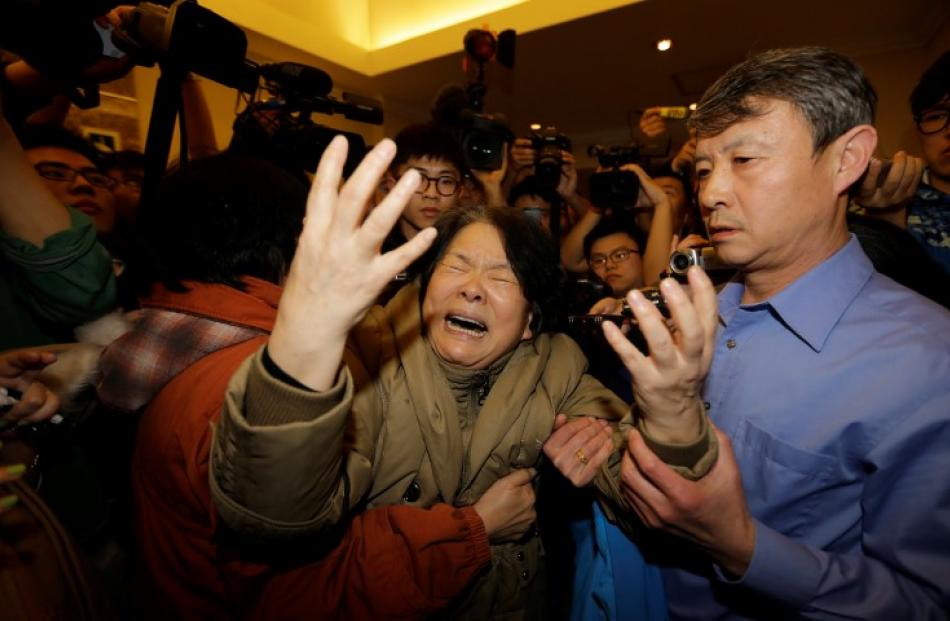 A family member of a passenger reacts after hearing the news that there were no survivors, at the...