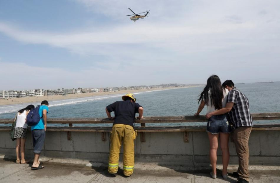 A firefighter looks over the pier during a search for victims of the lightning strike. REUTERS...