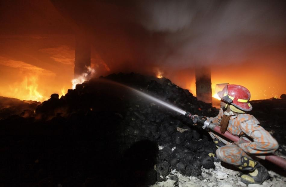A firefighter tries to control a fire at a garment factory in Savar, outskirts of Dhaka. Photo by...