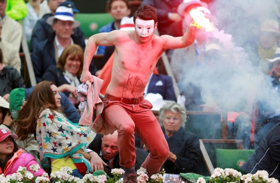 A flare-wielding Homen group protester jumps on to the court during the French Open final between...