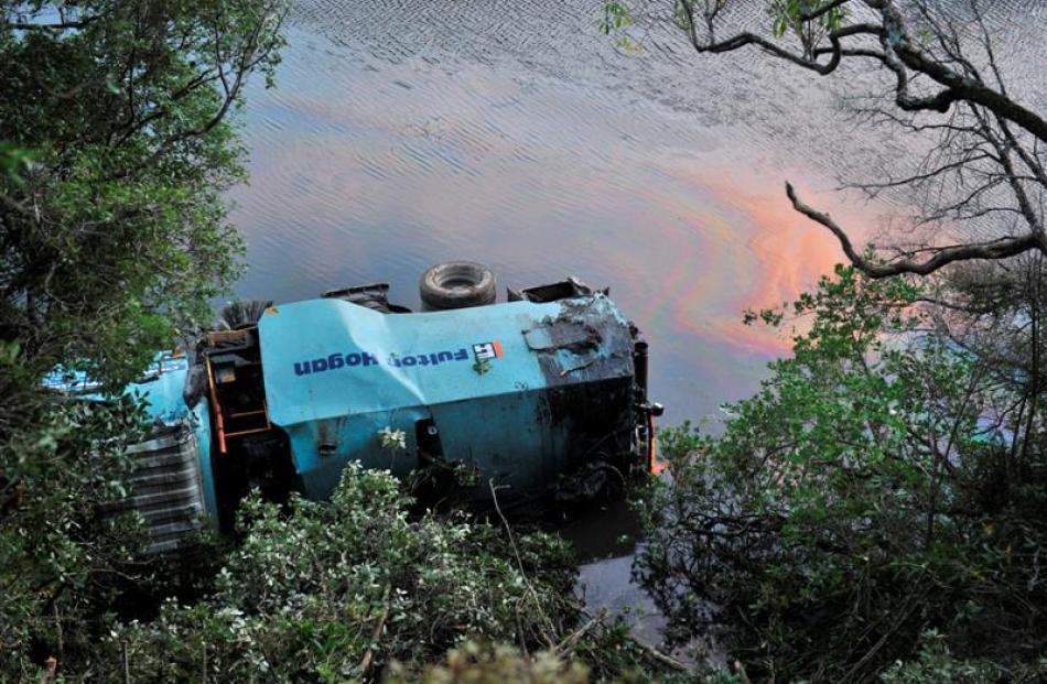 A Fulton Hogan truck lies in Otokia Creek  yesterday.
