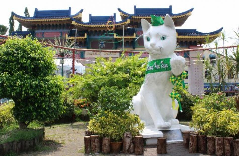 A giant cat statue - sporting a green ribbon to celebrate the end of Ramadan - guards the...