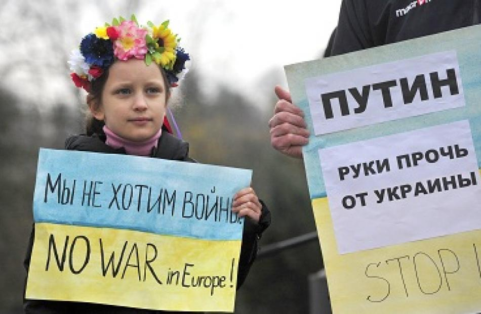 A girl and her father, both members of Slovenia's Ukrainian community, hold signs as they protest...