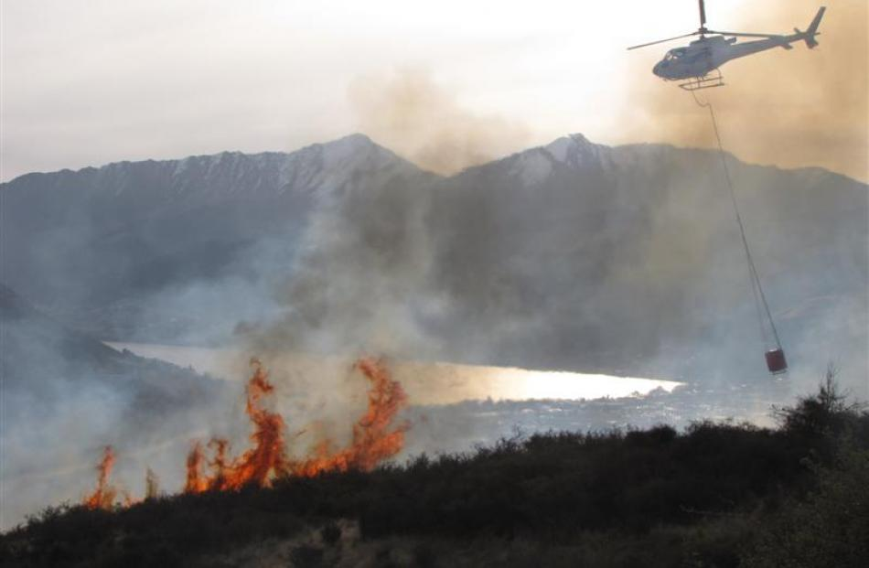 A helicopter attacks an out-of-control burn-off, covering an estimated 40ha, near the Remarkables...