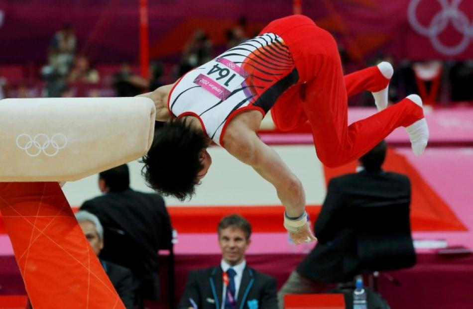 A judge watches as Kohei Uchimura of Japan falls off the pommel horse during the men's gymnastics...