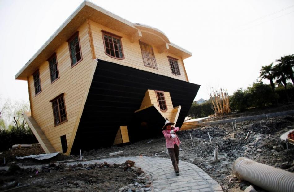 A labourer works at the upside-down house under construction at Fengjing Ancient Town in China....