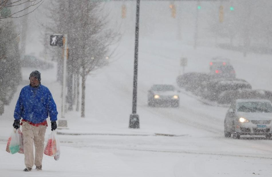A man carrying groceries makes his way to a bus stop as snow falls in Charlotte, North Carolina....